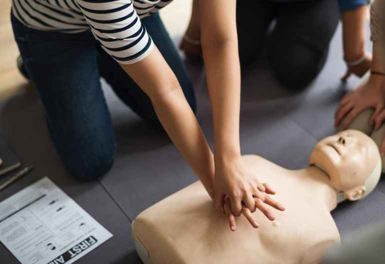 person performing cpr on dummy